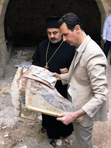 """In this photo released by the Syrian official news agency SANA, Syrian President Bashar Assad, right, holds a broken religious mosaic during his visit to the Christian village of Maaloula, near Damascus, Syria, Sunday April, 20, 2014. Assad toured a historic Christian village his forces recently captured from rebels, state media said, as the country's Greek Orthodox Patriarch vowed that Christians in the war-ravaged country """"will not submit and yield"""" to extremists. The rebels, including fighters from the al-Qaida-affiliated Nusra Front, took Maaloula several times late last year."""