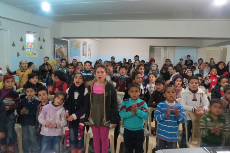 Syrian refugee children clap and sing about the birth of Jesus before their meal