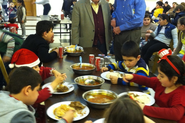Islam Ghatas and William Murray with children at a Christmas for Refugee event