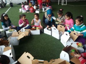 Children open their dinner boxes. At most events dinners are served on open plates and meals are hot, but that was not possible at this one