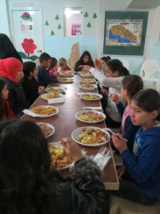 One of several tables of Syrian refugee children as they enjoy their hot Christmas meal