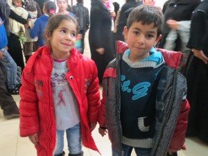 Two refugee children smile for the camera at a Christmas event in 2014