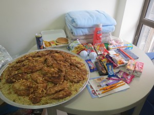 Adults were served fish and rice on plats from large platter. Children received hambeurger and fries in single serving trays. The contents of the children's gift bag and work books is shown with blankets.