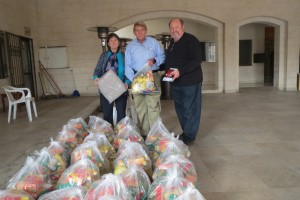 Nancy Murray, William Murray and Bob Armstrong with large bags of food staples to be distributed to the families of the children attending