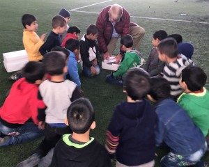 Christmas for Refugee director William Murray helps to pass out meals to one of the smaller groups the children formed by age and gender.
