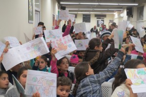 Children hold up coloring books for contest at one event.