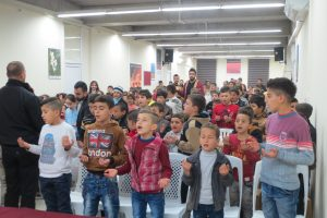 Children singing and praying together.