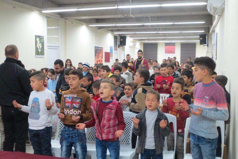Children singing and praying together.